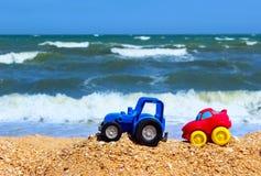 Små bilar på stranden Ungeleksaker på den tropiska sandstranden Bilar för leksak` s Arkivbild