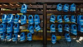 Små blåa flytvästar för ungar hänger i rad på bajset Fotografering för Bildbyråer