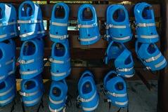 Små blåa flytvästar för ungar hänger i rad på bajset Arkivfoto