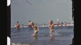 Små blonda tvilling- flickor som spelar ridningvågor arkivfilmer