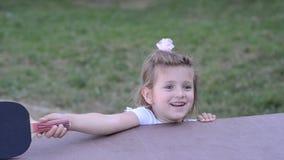 Små charmiga lyckliga flickabarnlekar knackar pong på gatan lager videofilmer