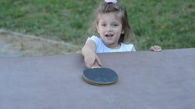 Små charmiga lyckliga flickabarnlekar knackar pong på gatan stock video