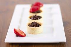 Små chokladtarts med den nya jordgubben arkivfoto