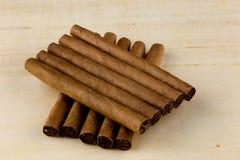 Små cigarrer på en trätabellöverkant arkivfoto