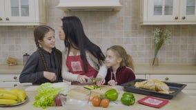 Små döttrar äter gurkan under deras moder som lagar mat salladen arkivfilmer