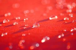 Små droppar av vatten på röd kanfas Arkivfoton