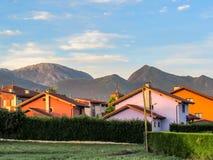 Små färgrika hus som omges av det gröna naturliga staketet med Cantabrian berg på bakgrund royaltyfri foto