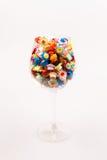 Små färgrika pappers- blommor i ett exponeringsglas av vin Royaltyfria Foton
