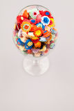 Små färgrika pappers- blommor i ett exponeringsglas av vin Royaltyfri Bild