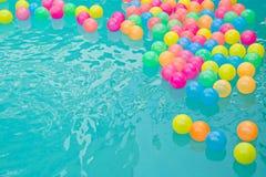 Små färgrika strandbollar som svävar i simbassäng, gör sammandrag begreppet för pölparti royaltyfri fotografi