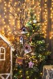 Små fågelhus som målades med snögubbear på ett tunt träd, dekorerade jul Arkivfoto
