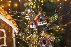 Små fågelhus som målades med snögubbear på ett tunt träd, dekorerade jul Royaltyfria Bilder