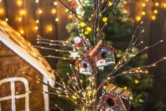 Små fågelhus som målades med snögubbear på ett tunt träd, dekorerade jul Arkivbilder