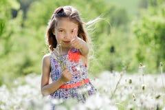 Små för vit flicka för maskrosfält behandla som ett barn härliga lyckliga gröna maskrosor för änggulingblommor som naturen parker Royaltyfri Foto