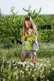 Små för vit pojke för flicka för maskrosfält behandla som ett barn lyckliga gröna maskrosor för änggulingblommor som naturen park Arkivfoto