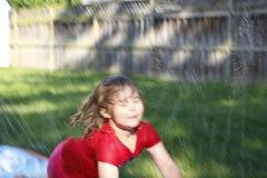 Små förskole- flickakörningar till och med en trädgård halkar och glider vattenglidbanan En rolig trädgårdaktivitet för unga barn royaltyfri foto