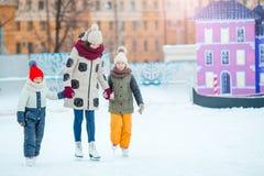 Små förtjusande flickor med modern som lär att åka skridskor på is-isbana Arkivbilder