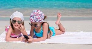 Små förtjusande flickor som spelar i telefon under Arkivbild