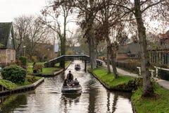 Små fartyg för folk som itu kryssar omkring på smala kanaler bland byggnader i den berömda byn Giethoorn arkivbild