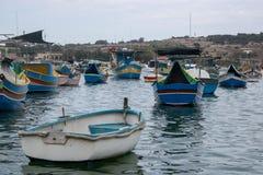 Små fartyg i Marsaxlokk i en molnig dag royaltyfri foto