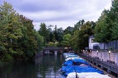Små fartyg med raincovers i kanal med träd- och vattenreflexionen för att fiska och att segla Arkivbilder