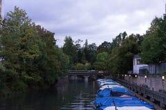 Små fartyg med raincovers i kanal med träd- och vattenreflexionen för att fiska och att segla Arkivfoton