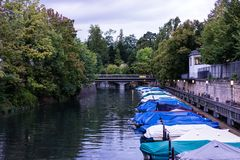 Små fartyg med raincovers i kanal med träd- och vattenreflexionen för att fiska och att segla Royaltyfria Bilder