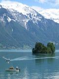 Små fartyg på Brienzersee sjön, Schweiz, med snö täckte det Rothorn berget som bakom stiger upp Arkivfoto