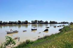 Små fartyg på den Guadalquivir floden, som den passerar till och med Coria del Rio de Janeiro, det Seville landskapet, Andalusia, royaltyfria foton