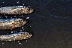 Små fiskar med salt på tabellen Arkivfoton