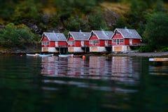 Små fiskfartyghus på Flam, Norge Lutandeförskjutningseffekt Klassiska röda rorbukabiner nära flodbanken Fiskarehus Arkivfoton