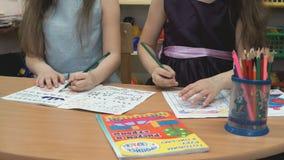 Små flickor drar bilderna i förskriftsböckerna stock video