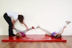 Små flickor går en övning på ett mattt, ben upp Royaltyfri Foto