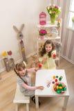 Små flickor göras av påsk - de målar, dem drar i rummet arkivbild