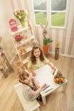 Små flickor göras av påsk - de målar, dem drar i rummet royaltyfri fotografi