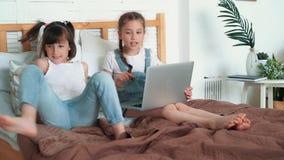 Små flickor håller ögonen på något på bärbara datorn och diskuterar känslomässigt den, ultrarapid arkivfilmer