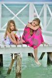Små flickor i färgrik klänning på den vita träpir Fotografering för Bildbyråer