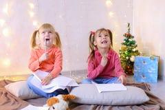 Små flickor i förväntan av ferier för ` s för det nya året gör önska Arkivbilder