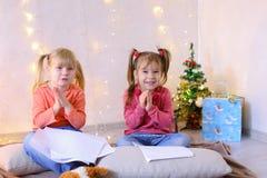 Små flickor i förväntan av ferier för ` s för det nya året gör önska Arkivfoton