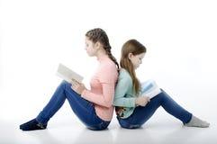 Små flickor läste böcker tillbaka för att dra tillbaka på vit Royaltyfria Foton
