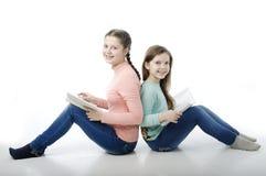 Små flickor läste böcker tillbaka för att dra tillbaka på vit Arkivfoto
