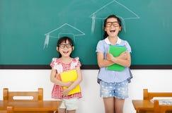 små flickor med avläggande av examenbegrepp i klassrum Royaltyfri Bild