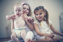 Små flickor med behandla som ett barn brodern poserar till kameran Royaltyfri Foto