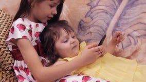 Små flickor med mobilen Systerlek med en mobiltelefon Barnen spelar på soffan klär flickor lager videofilmer