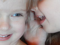 Små flickor som berättar hemligheter som viskar tvilling- systrar royaltyfri foto