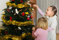 Små flickor som dekorerar julgranen Arkivfoton
