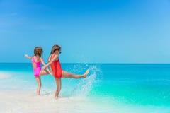 Små flickor som har gyckel på den tropiska stranden som tillsammans spelar på grunt vatten Royaltyfria Foton