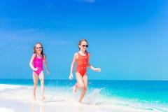 Små flickor som har gyckel på den tropiska stranden som tillsammans spelar på grunt vatten Royaltyfria Bilder