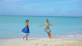 Små flickor som har gyckel på den tropiska stranden under att spela för sommarsemester stock video
