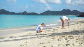 Små flickor som har gyckel på den tropiska stranden under sommarsemestern som tillsammans spelar arkivfilmer